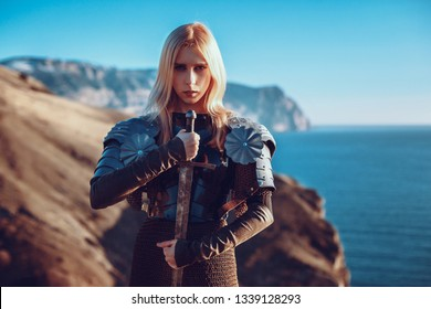 The cute female warrior attacking with sword. Fantasy photo. Beautiful girl knight in the mountains watching the sunset over the sea