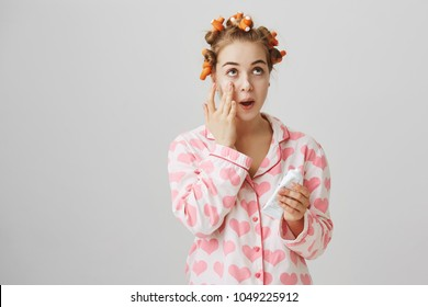 Cute feminine european girl wearing hair-curlers and pyjamas applying cream on clean skin, looking up and standing over gray background. Fashionable woman takes care of her appearance