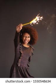 Cute festive girl with burning sparkler against dark background