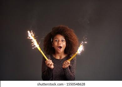 Cute festive girl with burning sparklers against dark background