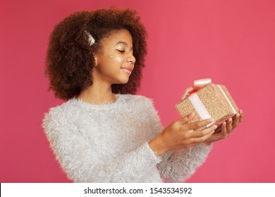 Cute festive girl holding a shiny gift box against pink background