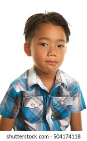 Cute Filipino Boy on a white background. He is staring  at the camera with a serious,blank expression