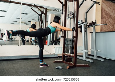 cute fit girl doing exercises on the simulator