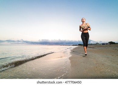 Cute fit tanned happy girl in sport top and leggings jogging on beach at sunset. Fitness, workout and healthy lifestyle concept. Blue sky in the morning with clouds