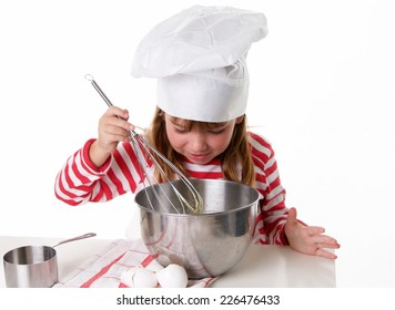 Cute five year old girl wearing a chef hat and apron is mixing ingredients in a metal mixing bowl on a white background