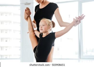 Cute flexible little balerina stretching legs with help of her teacher in ballet studio