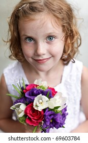 Cute flower girl holding a small bouquet of flowers