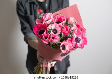 cute flowers. beautiful bouquet of pink anemones in woman hand. the work of the florist at a flower shop. A small family business