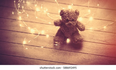 cute fluffy teddy bear and bright garland on the wonderful brown wooden background
