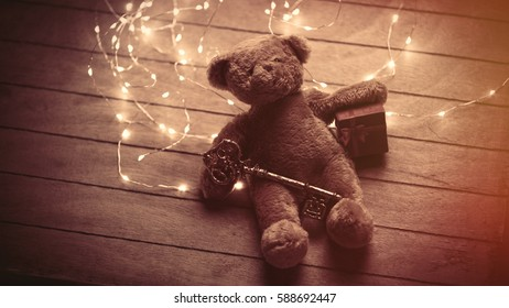 cute fluffy teddy bear with gift and golden key and bright garland on the wonderful brown wooden background