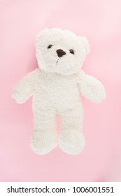 Cute fluffy white teddy bear on romantic and vintage of pink colour background.