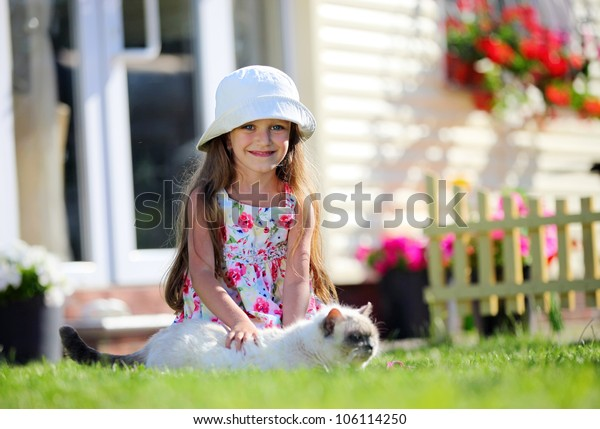 Cute four-year girl smiling brightly and stroking her cat, looking at camera, outdoors