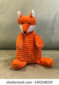 Cute fox doll is sitting on the sofa.