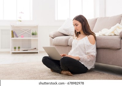 Cute freelancer girl working on laptop. Young woman in casual sitting on the floor in light appartment