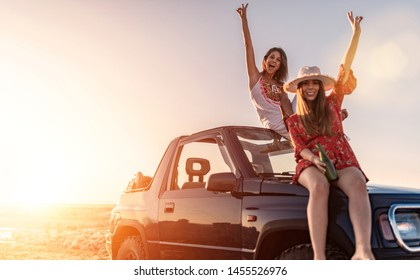 cute friends enjoying a sunset on the beach having a good time smiling