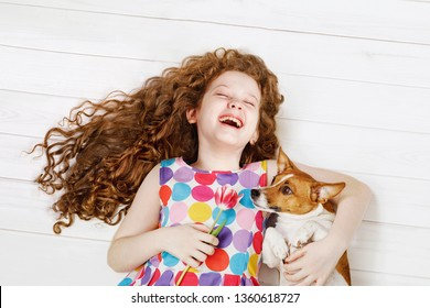 Cute friends, laughing girl embracing a dog, laying on a warm wooden floor.