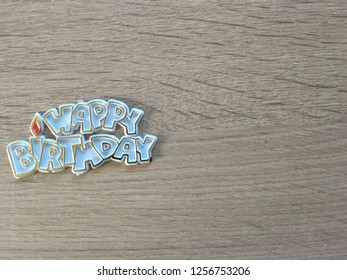 """Cute front wording """"Happy Birthday"""" made by plastic on soft brown wood surface background with copy space for illustration or montage for birthday greeting."""