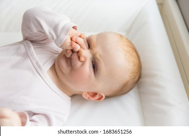 Cute frowning red-haired baby pulling face. Close-up portrait of newborn child laying down in dissatisfaction. Nursery, newborn kid and infancy concept