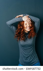 Cute fun loving attractive young woman with gorgeous long curly red hair standing with her hands clasped above her head and a big grin over a dark studio background