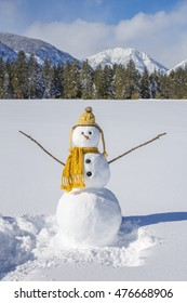 Cute fun snowman with knit hat and scarf in snowy cold winter landscape field with mountains and blue sky