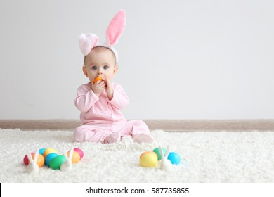 Cute funny baby with bunny ears and colorful Easter eggs at home
