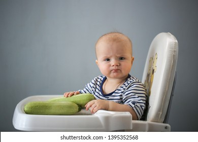cute funny baby eats raw zucchini in children's chair, first feed and organic, gray plain background, funny emotions