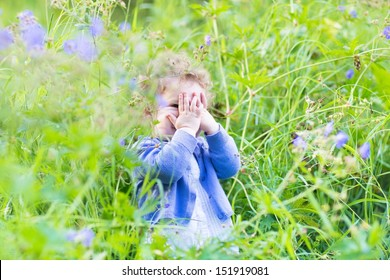 Cute funny baby girl playing hide and seek in the garden with blue and purple flowers