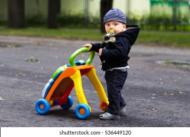 Cute funny baby with learning walker in the park