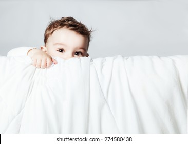 Cute and funny baby is looking and climbing on blanket over white background. Copy space.