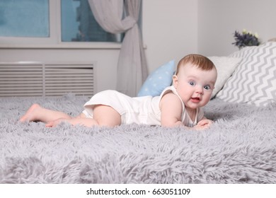 Cute funny baby in white lies on bed with pillows in bedroom