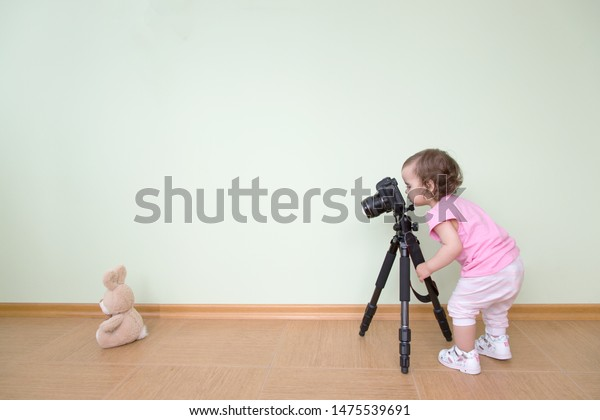 Cute funny beautiful baby photographs her bunny. The baby stands and holds a DSLR camera on a tripod against the background of a green wall. Concept novice beginner photographer, first steps.