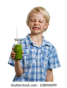 A cute funny boy is pulling a face looking at a green smoothie or juice. Isolated on white.