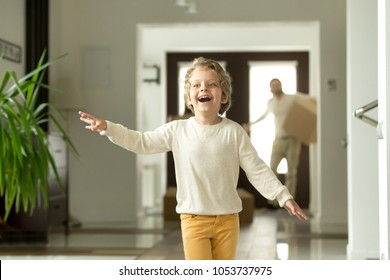 Cute funny boy running in hallway exploring big luxury house relocating with parents, excited child son jumping playing entering new modern home, happy kid enjoying moving day with family concept
