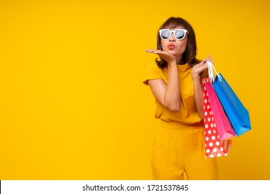 Cute and funny cheerful woman standing in yellow casual cloth style show empty hand for product on sale and holding colorful shopping bag.