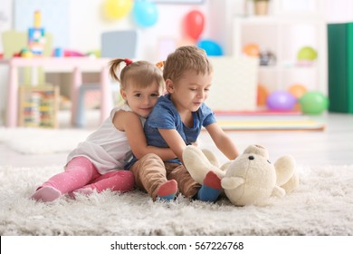 Cute funny children playing with teddy bear at home