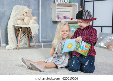 Cute funny children sitting on carpet with book