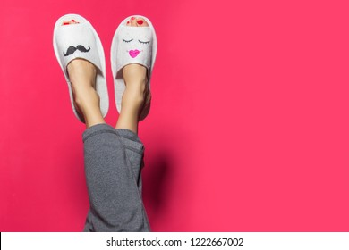 Cute funny couple on pink red. Woman wearing bright pants lying with legs upwards wearing unusual slippers with faces of man and woman