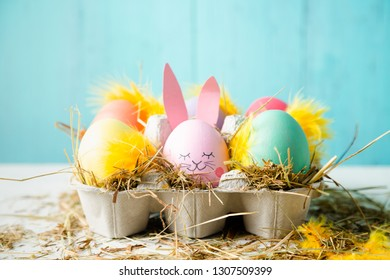 Cute and funny easter eggs with an egg decorated as a rabbit against a turquoise background