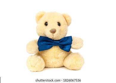 Cute funny fluffy yellow teddy bear kids favourite stuffed toy with small black plastic eyes and dark blue satin bow tie sitting isolated on white background.