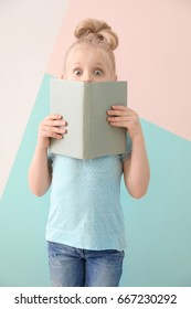 Cute funny girl with book on color background