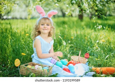 Cute funny girl with Easter eggs and bunny ears at garden. easter concept. Laughing child at Easter egg hunt. Child in park with basket full of eggs, spring concept