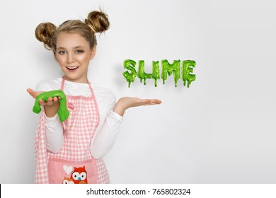 Cute funny girl with slime in the kitchen. The girl cooks and bakes her muffins, makes a cake and slime.