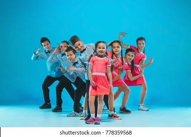 Cute funny girls and boys dancing on blue background