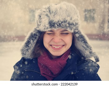 cute funny happy  girl in a fur cap  laughing under the snow, image with instagram retro effect