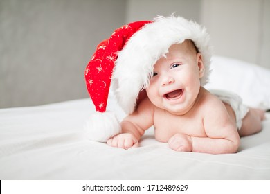 Cute funny infant baby in a big Santa Claus hat looking at camera on a white bed. New Year. Cheerful kid. Copyspace