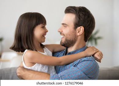 Cute funny kid girl laughing looking at father talking having fun with happy loving dad, little child daughter embracing daddy enjoying good time together, positive emotion and sincere communication