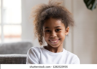 Cute funny little african american girl looking at camera, smiling mixed race child posing for portrait at home, preschool positive black kid with happy face headshot, orthodontic malocclusion