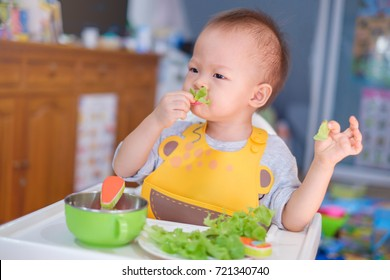 Cute funny little Asian 20 months toddler baby boy child sitting in high chair eating salad,Healthy nutrition and Bio vegetable as solid food for infant. Kid eat vegetables, Eating healthy concept