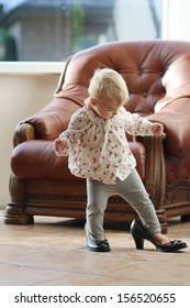 Cute funny little baby girl walks at home trying mom's black high heel shoes