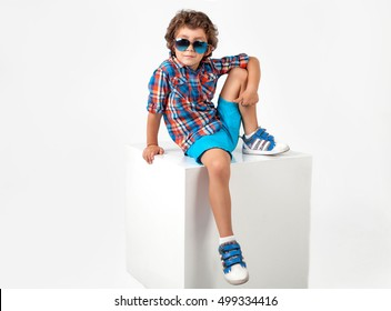 Cute and funny little boy in plaid shirt and blue shorts and sunglasses. Fashion children. White background